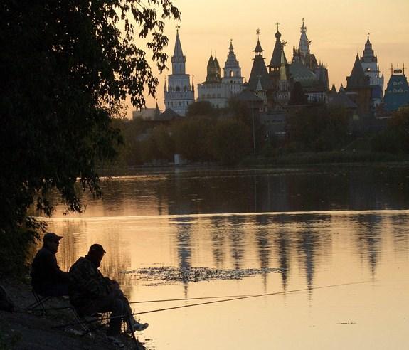 два рыбака с удочками на озере