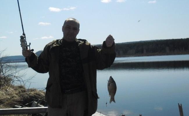рыболов с донкой из бассмании и пойманным карасем
