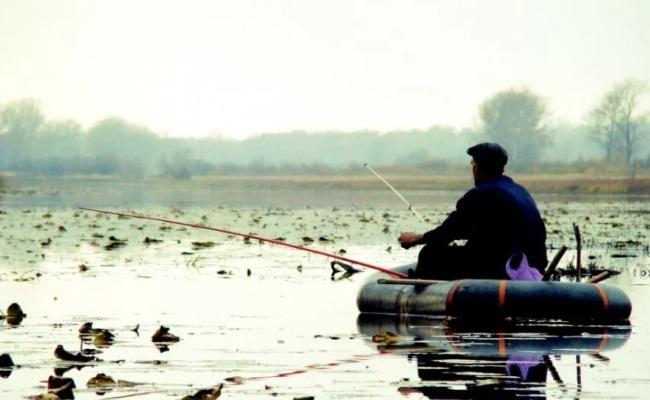 рыболов с лодки ловит рыбу